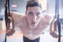 Young man exercising at rings in gym — Stock Photo
