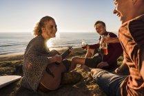 Tre amici che suonano la chitarra al mare — Foto stock