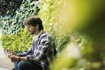 Молодой человек сидит перед зеленой стеной завода, используя цифровой планшет — стоковое фото