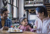 Family at kitchen table with birthday cup cakes — Stock Photo