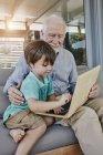 Portrait of senior man with grandson using laptop — Stock Photo