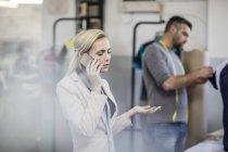 Модный дизайнер на мобильном телефоне в мастерской — стоковое фото