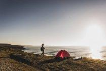 Девушка с красной палатку и серфинга в море в вечерние сумерки. — стоковое фото