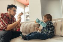 Father and son playing together with socks on couch — Stock Photo