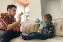 Pai e filho jogando junto com meias no sofá — Fotografia de Stock