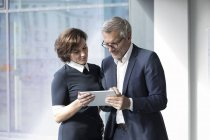 Businessman and businesswoman sharing tablet — Stock Photo