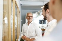 Smiling businessman looking at colleagues in office — Stock Photo
