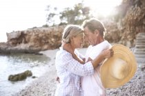 Active cute senior couple hugging on beach — Stock Photo