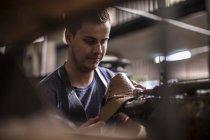 Shoemaker working on shoe in workshop — Stock Photo
