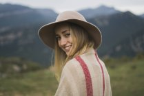 Portrait of smiling young woman wearing hat standing in nature — Stock Photo