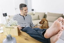 Relaxed man with dog at home using tablet — Stock Photo