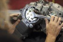 Крупным планом механика работает на двигатель мотоцикла в мастерской — стоковое фото