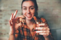 Young woman painting hippopotamus plastic figure with gold paint — Stock Photo