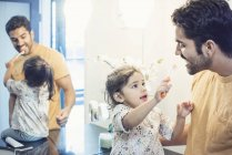 Toddler daughter playing with toothbrush washing her father teeth — Stock Photo