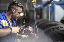 Manutentore maschio lavorando sul pneumatico in fabbrica — Foto stock