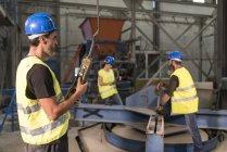 Працівник за допомогою керування в залі заводу — стокове фото