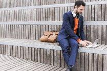 Homme d'affaires assis sur un escalier et utilisant une tablette numérique, New York, États-Unis — Photo de stock