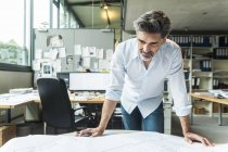 Architect working on ground plan in office — Stock Photo