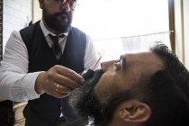 Barber cutting man beard in barbershop saloon — Stock Photo