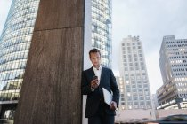 Germany, Berlin, Potsdamer Platz, businessman looking at his smartphone in the evening — Stock Photo