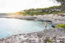 Беременная женщина, стоящая на скале в море с распростертыми руками — стоковое фото