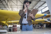 Female pilot talking on a phone in airfield hangar — Stock Photo