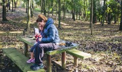 Mother and little daughter sitting at picnic place in the forest playing with smartphone — Stock Photo