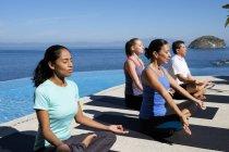 Yoga groupe d'exercice sur le front de mer station — Photo de stock