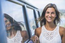 Портрет усміхнений молода жінка притулившись кемпінг автобус — стокове фото