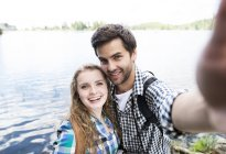 Young couple on a hiking tour at a lake taking a selfie — Stock Photo