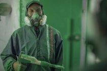 Художники, распыляющие стальные компоненты в аэрозольной кабинке завода — стоковое фото