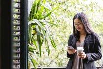 Giovane donna in piedi alla finestra e la lettura di messaggi — Foto stock