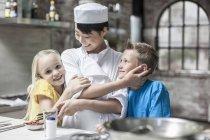 Irmãos abraçam chef na aula de culinária — Fotografia de Stock