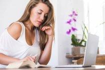 Giovane donna con libro e laptop a casa — Foto stock