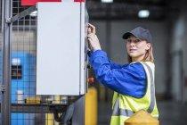 Arbeitnehmerin, die Maschine im Werk in Betrieb — Stockfoto