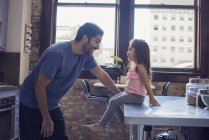 Father and daughter sitting on kitchen table looking one at other — Stock Photo