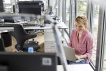 Привлекательная блондинка улыбающаяся женщина с ноутбука в офисе — стоковое фото