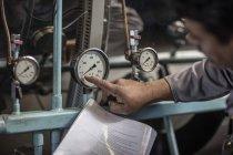 Kaukasier kontrolliert Druck auf Maschine — Stockfoto