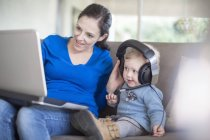 Mother with baby girl wearing headphones using laptop at home — Stock Photo
