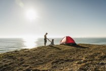 Young couple camping at seaside, drinking beer by tent — Stock Photo