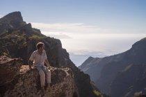 Spain, Tenerife, Teno Mountains, Masca,  man sitting on the cliff — Stock Photo