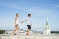Slovakia, Bratislava, senior couple walking barefoot on a wall in front of the city — Stock Photo
