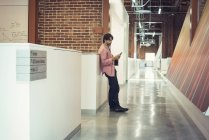Businessman standing corridor reading messages — Stock Photo