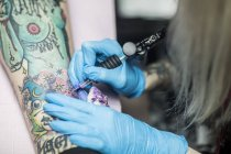 Femelle de tatoueur tatouage une jambe — Photo de stock