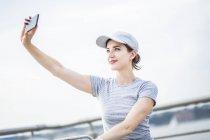 Frau in Baseball-Kappe nehmen Selfie mit Handy — Stockfoto