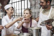 Studentin Geschmack aus Topf im Kochkurs — Stockfoto