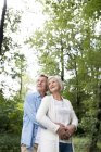 Coppie maggiori sveglie attive che abbracciano insieme nel parco — Foto stock