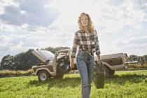 Woman walking with petrol can on field next to pick up truck — Stock Photo