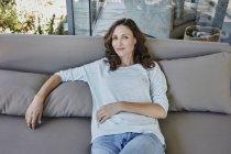 Portrait of smiling mature woman lying on sofa — Stock Photo