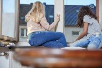 Две девушки смотрят в окно дома — стоковое фото